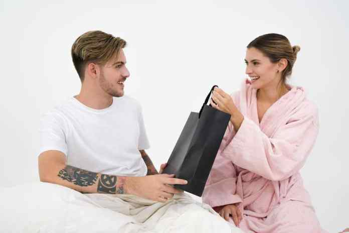Boyfriend giving gift to girlfriend, surprise